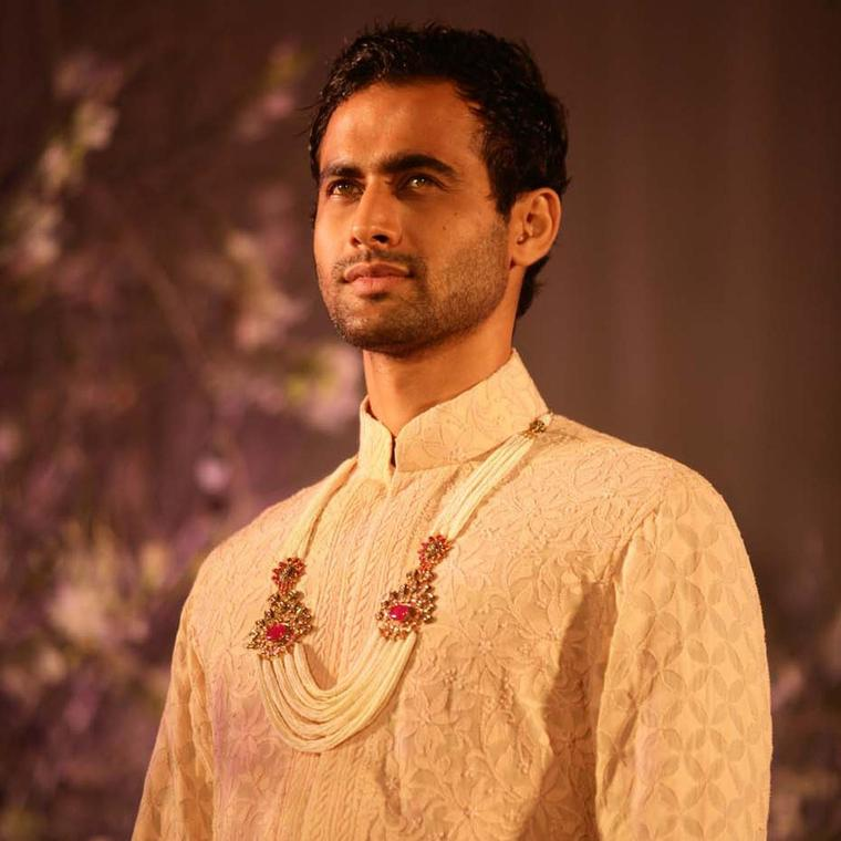 A model sporting a nehru jacket with a multi-string pearl necklace featuring kundan polki and gem-set brooches by Anmol Jewellers.