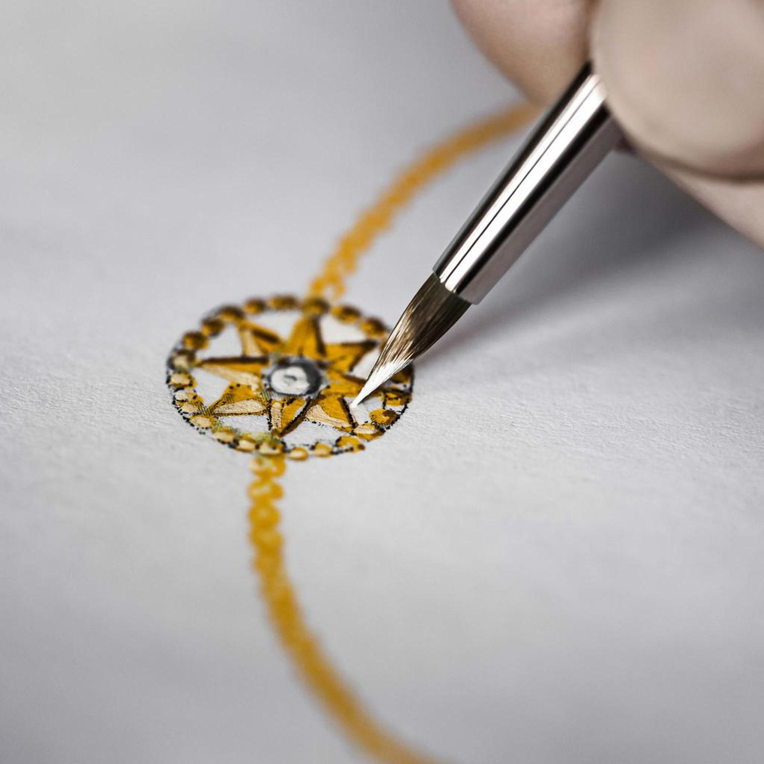 An artist adds fine detail to a gouache of the Rose des Vents bracelet, with its distinctive star motif.