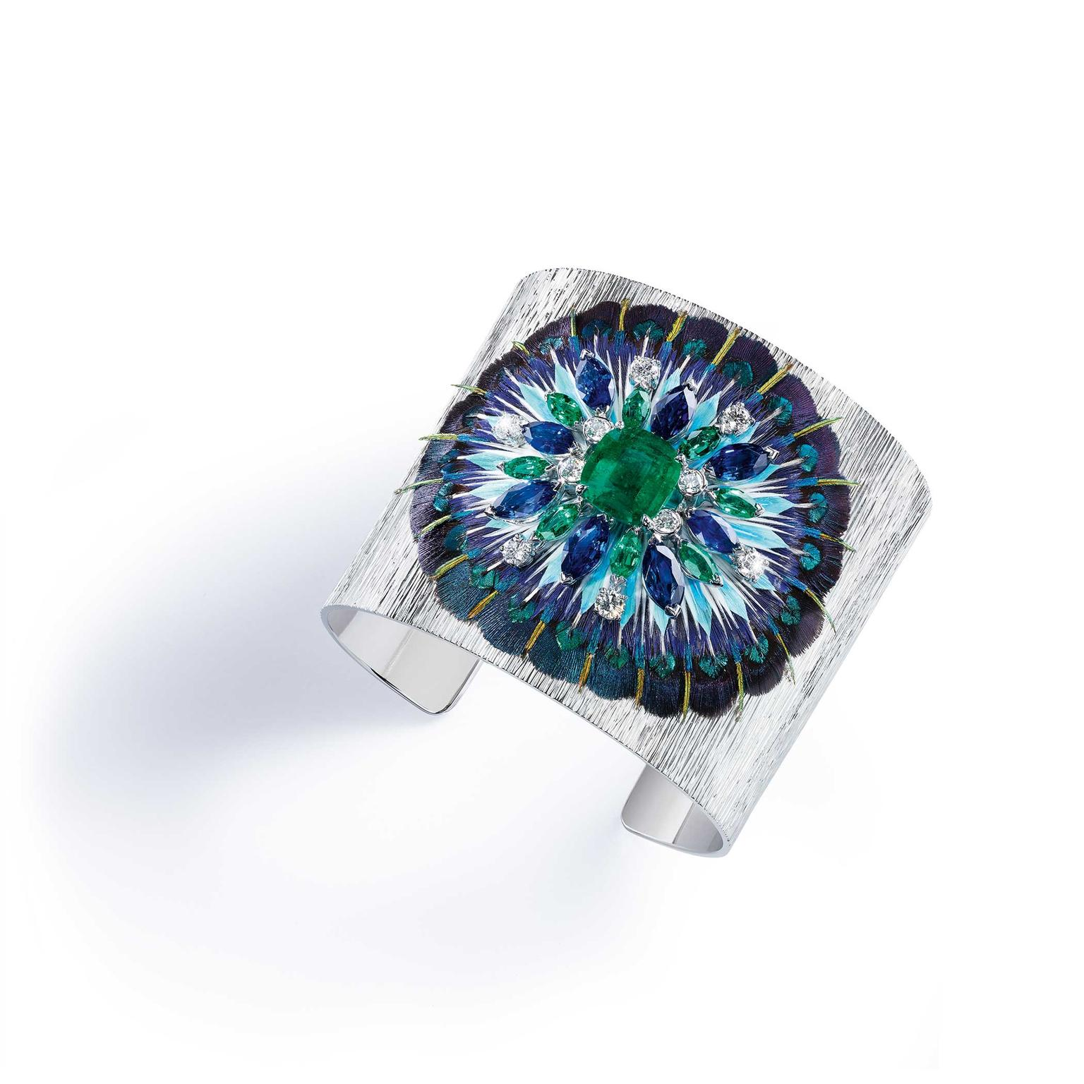 Piaget Serenissima cuff with emeralds, sapphires and diamonds on a bed of feathers