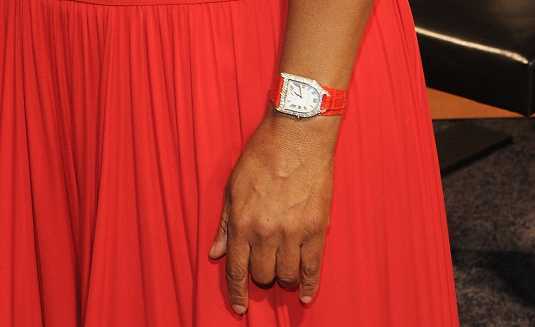 A closer look at the watch on Oprah's wrist reveals a Ralph Lauren Stirrup with diamonds and orange strap to match the dress.