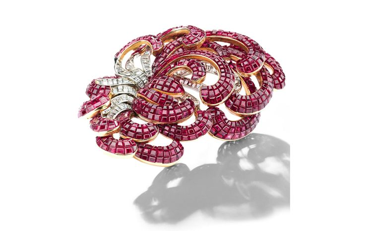 A Mystery-set ruby and baguette-cut diamond scroll brooch, by Van Cleef & Arpels, 1930s. Estimate: SFr. 270,000-450,000 (US$ 300,000-500,000)