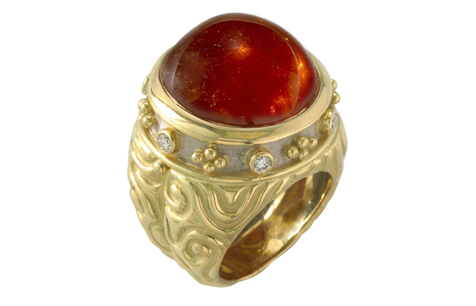 ELIZABETH GAGE, Charlemagne Ring, a glowing round orange cabochon garnet surrounded with diamonds and bead detail in yellow and white gold, with carved molten gold sides. £11,400