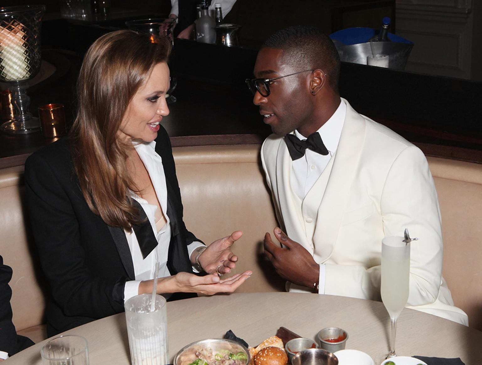 Deep in conversation with the sharply dressed Tinie Tempah, Angelina Jolie gave a flash of her diamond watch tucked under her shirt cuff