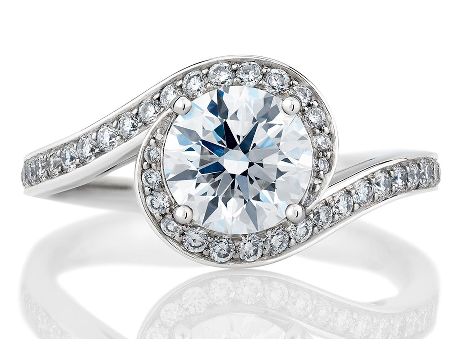 De Beers' Caress solitaire engagement ring incorporates a curved diamond pave´ that appears to embrace the central diamond