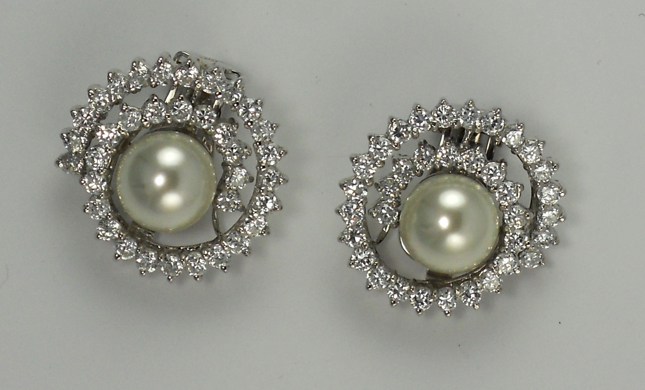 CIRO. White Shell Pearl set in sterling silver rhodium plate swirl with white cubic zirconia brilliant cut stones.jpg