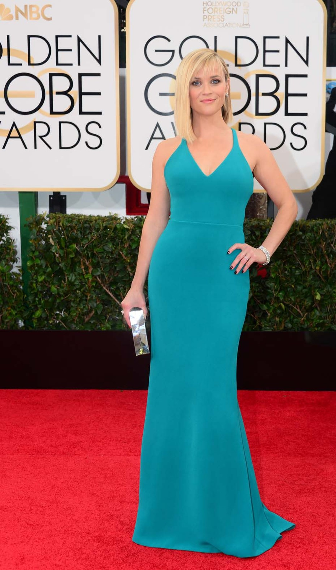 Golden Globes 2014 presenter Reese Witherspoon in figure-hugging turquoise dress and jewels by Harry Winston: a 10ct emerald-cut diamond ring, three stacked Diamond Line bracelets, and diamond ear studs