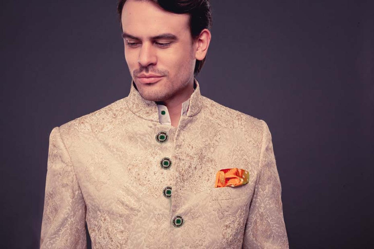 A sherwani by fashion designer Raghavendra Rathore featuring diamond and emerald buttons.