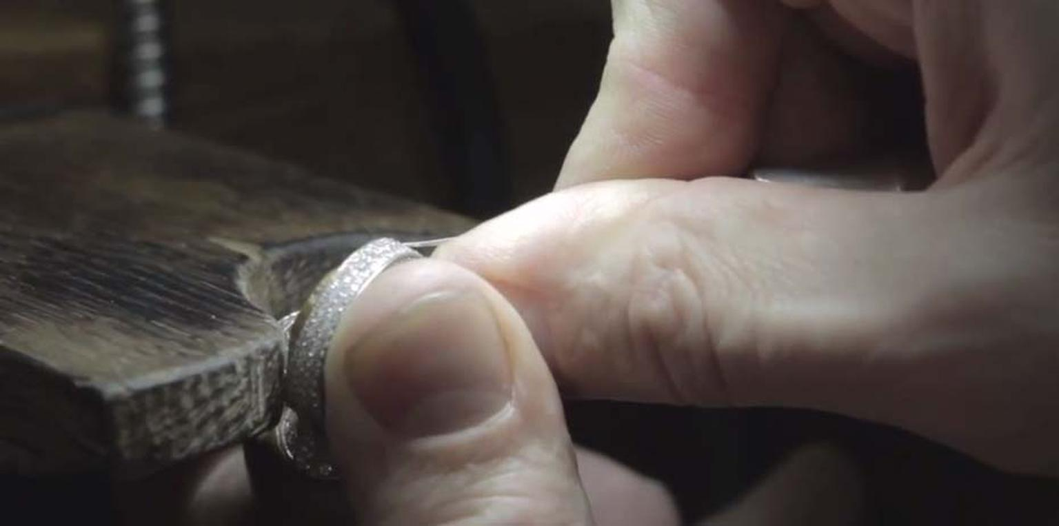 A Louis Vuitton jeweller works on perfectly setting a row of diamonds.