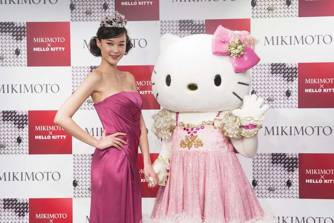 Hello Kitty strikes a pose with a model wearing the Hello Kitty tiara at the Mikimoto x Hello Kitty launch event at Mikimoto's flagship boutique in Tokyo