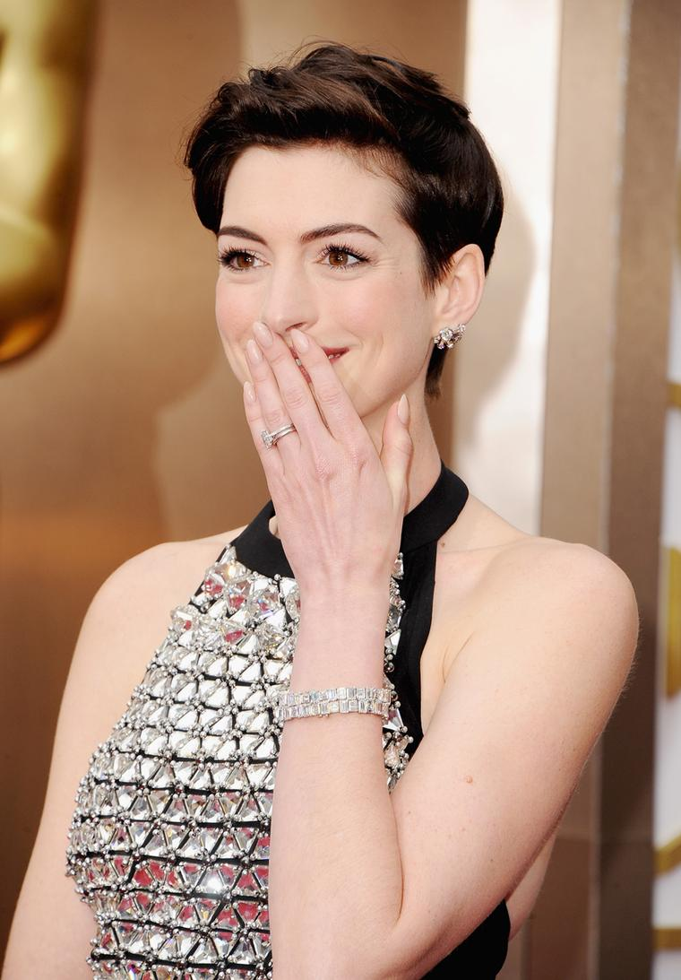 Anne Hathaway on the Oscars red carpet in matching Neil Lane diamond and platinum bracelets valued at US$1 million, a platinum, emerald and diamond ring and platinum and diamond stud earrings, all by Neil Lane