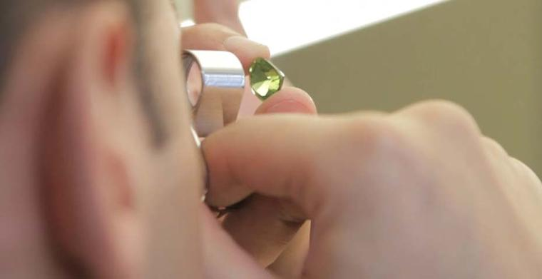 Examining a gemstone through a jewellery loupe at Van Cleef & Arpels L'Ecole