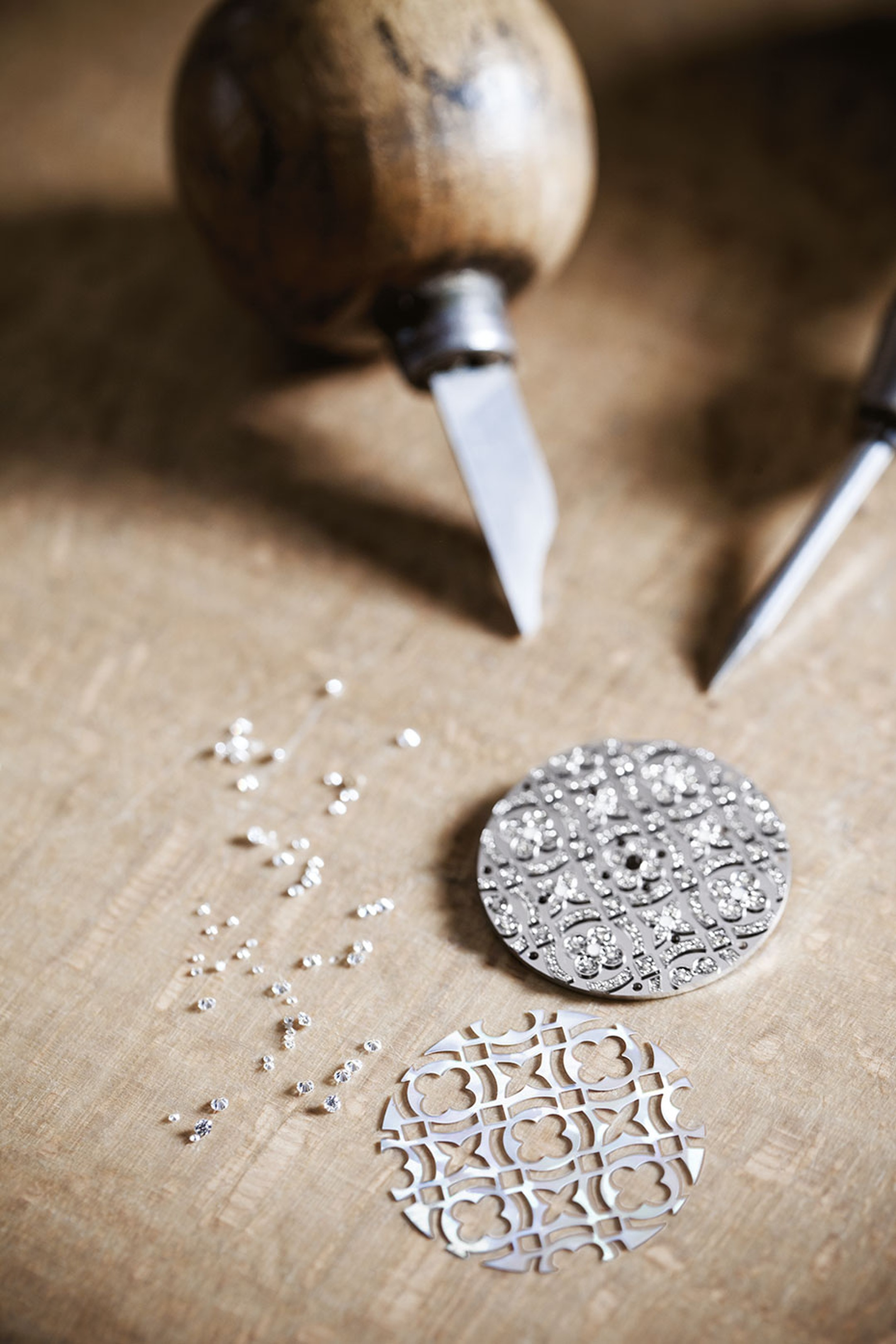 A craftsman at Louis Vuitton's watchmaking atelier setting diamonds on the dial of a Dentelle de Monogram watch