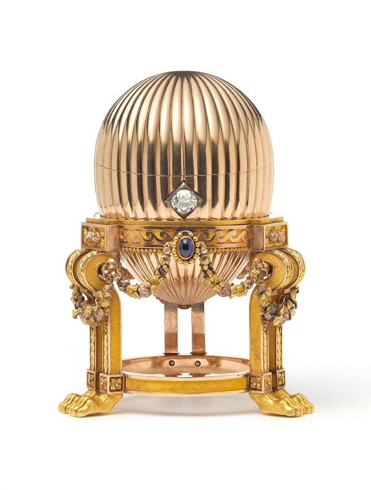 The yellow gold Imperial Faberge Easter Egg contains a Vacheron Constantin watch with diamond set gold hands. The egg sits on a stand with lions paw feet, decorated with gold garlands and three cabochon blue sapphires topped with rose diamond set bows.