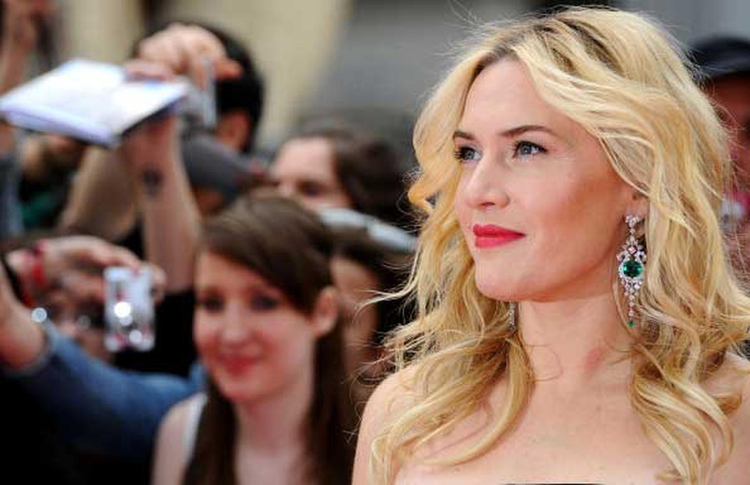 Kate Winslet looks radiant in David Morris emerald and diamond earrings as she says hello to fans at the London premiere of her new film, Divergent