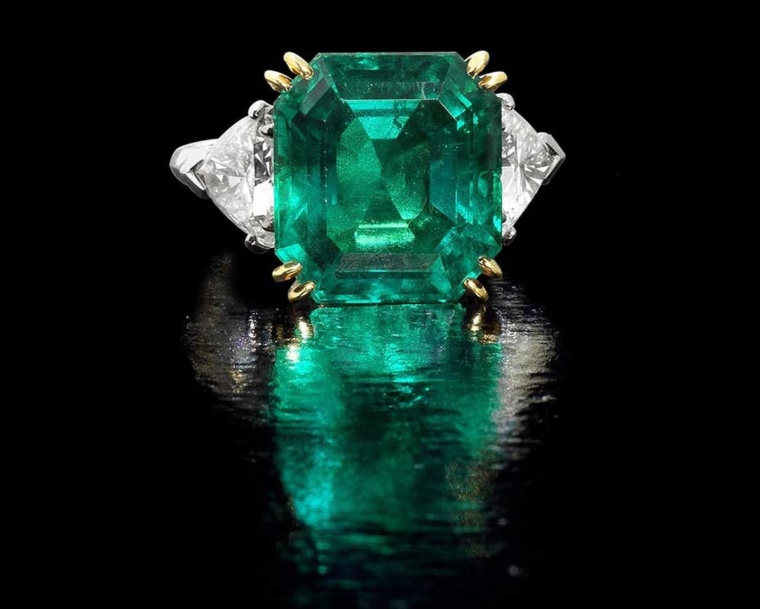 Lot 192, a Colombian emerald and diamond ring. The octagonal step-cut emerald weighs 10.49ct, flanked by triangular-cut diamonds of approximately 2.00ct. Sold for £362,500  (estimate: £150,000-£200,000)