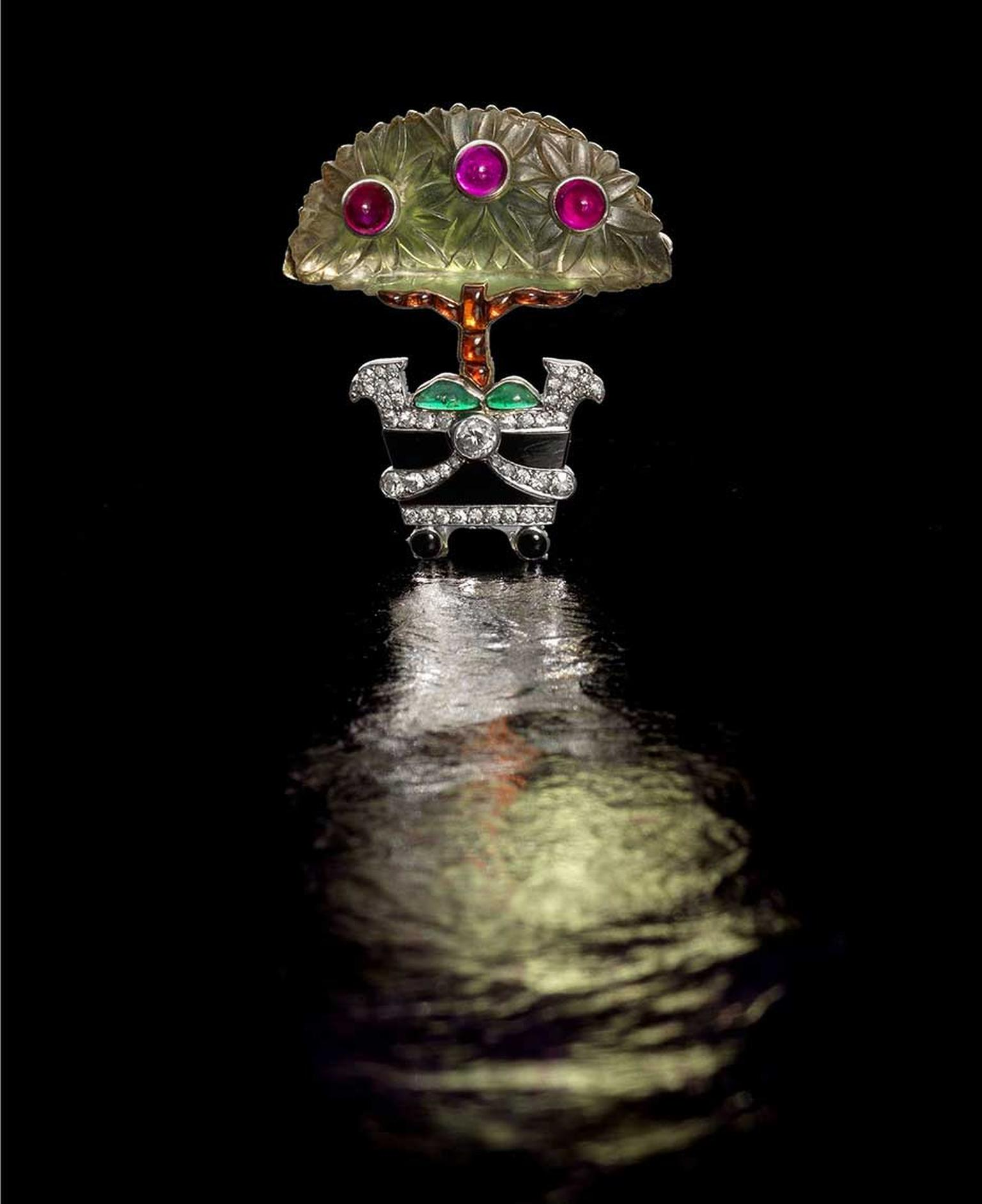 "Lot 183, a frosted rock crystal and gem-set Cartier ""Orange Tree"" brooch dating from 1914, with three cabochon ruby ""fruits"", a buff-top calibré-cut citrine trunk and cabochon emerald foliage at its base (estimate: £15,000-£20,000)"