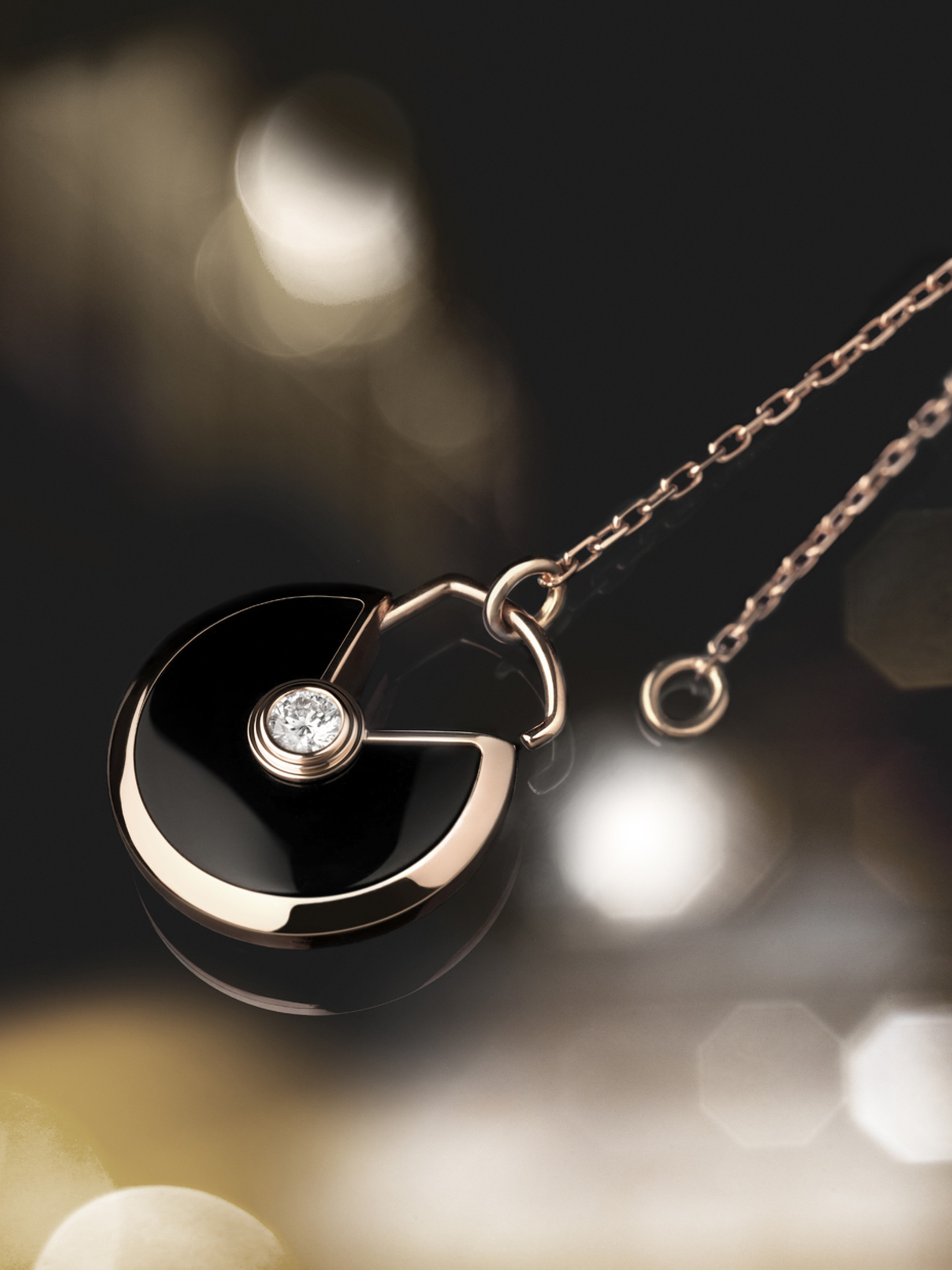 Amulette de Cartier small pink gold pendant with onyx surrounding a brilliant-cut diamond.