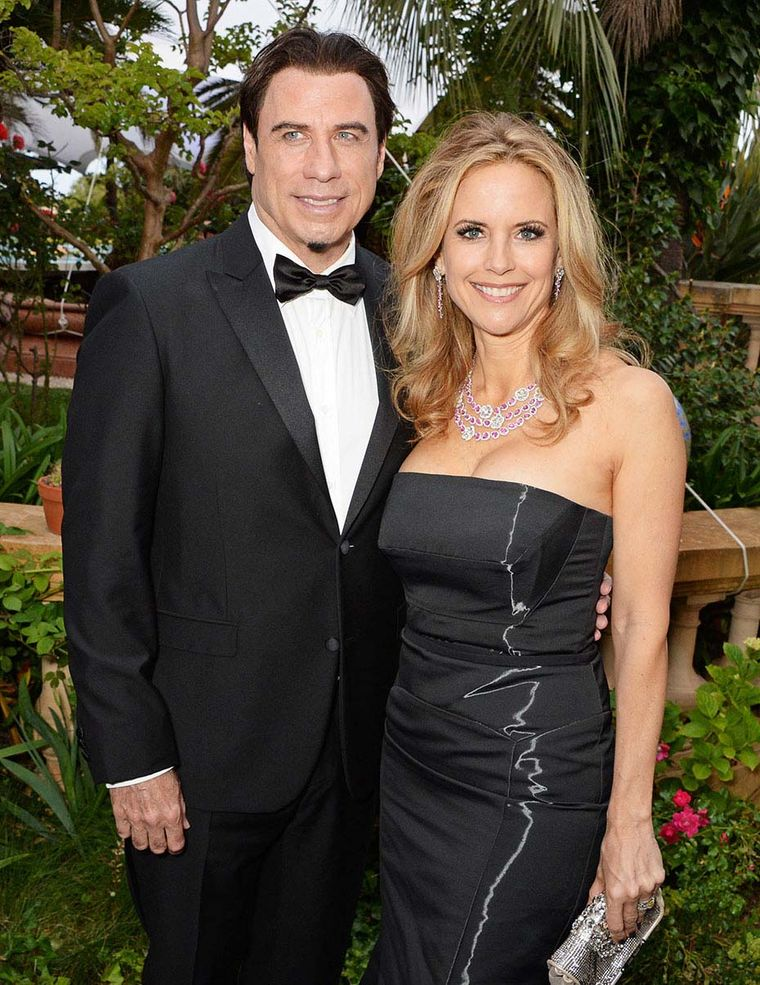 John Travolta looking dapper alongside Kelly Preston, who brightened the seventh day of the Cannes Film Festival in a hot-pink pink sapphire and diamond Avakian necklace and earrings