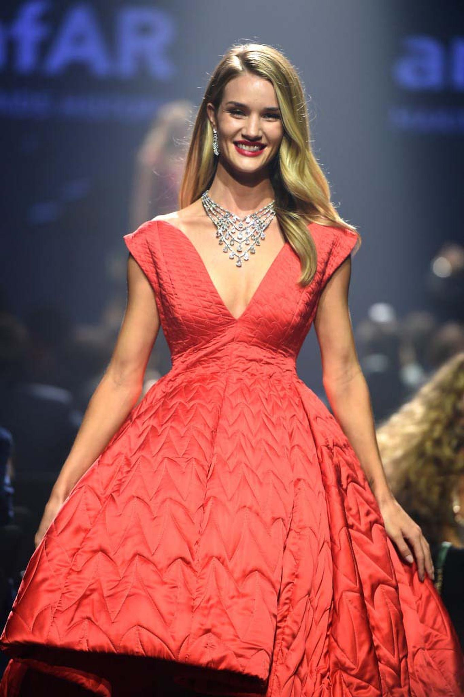 Rosie Huntington-Whiteley beams as she walks down the catwalk in Bulgari jewels. A red-themed fashion show curated by Carine Roitfeld formed part of the 2014 amfAR charity fundraiser in Cannes