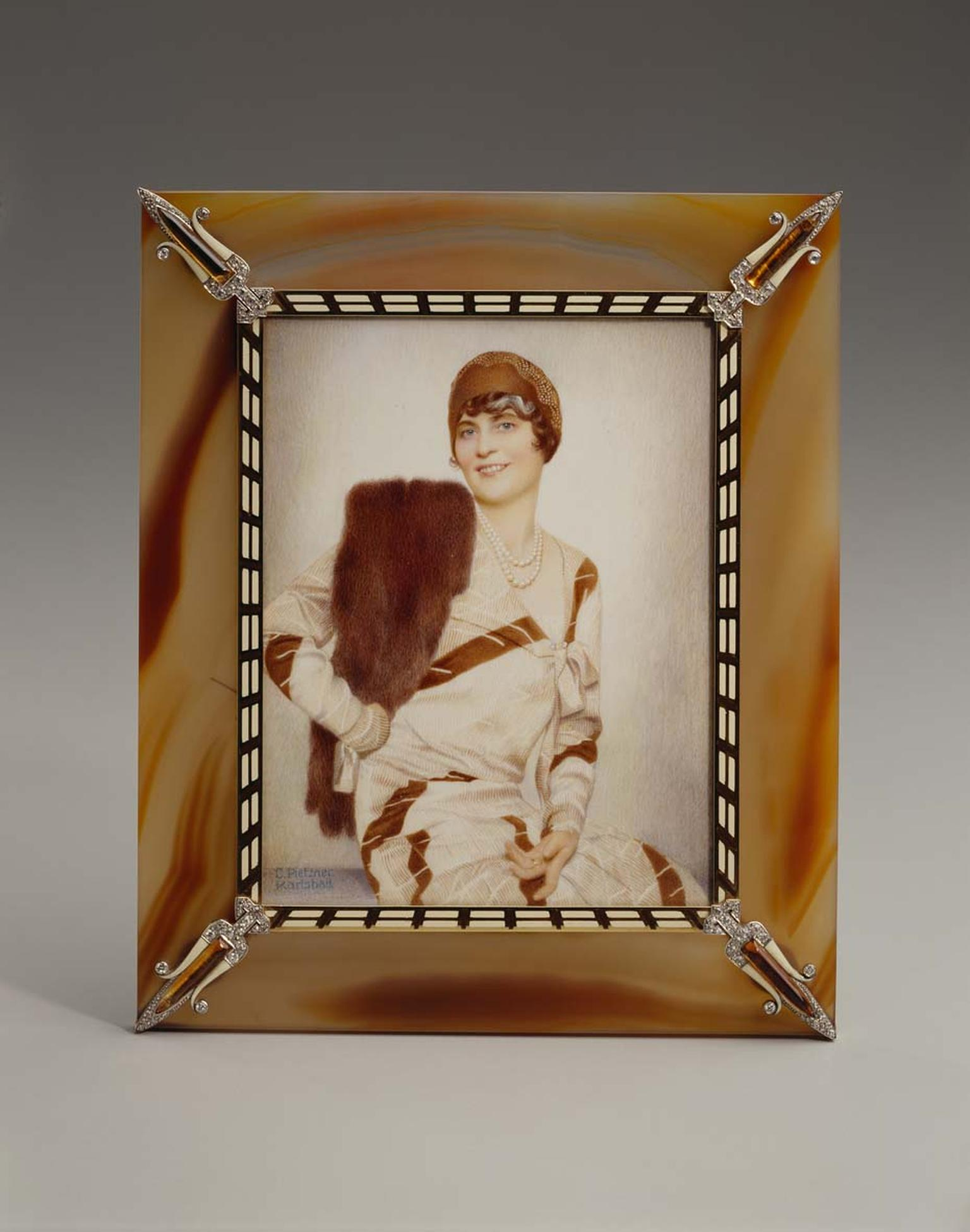 Cartier gold frame with agate, enamel, citrine quartz and diamonds displaying a photo of Marjorie Merriweather Post by C. Peitzner in watercolor on ivory. Image: Courtesy Hillwood Estate, Museum and Gardens