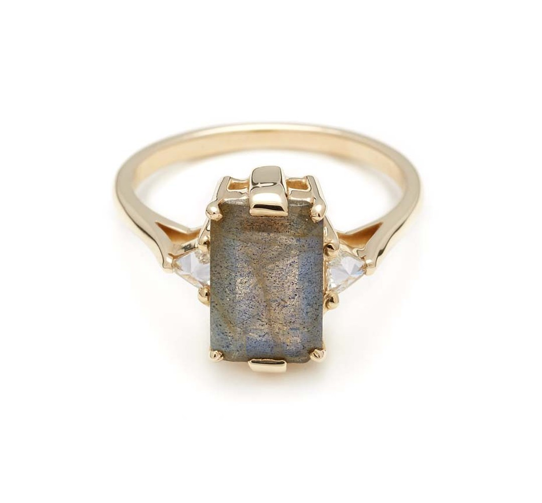 Anna Sheffield Bea three-stone engagement ring with an emerald-cut labradorite set in a signature bridal signature basket, flanked by inverted white diamond trillions in yellow gold