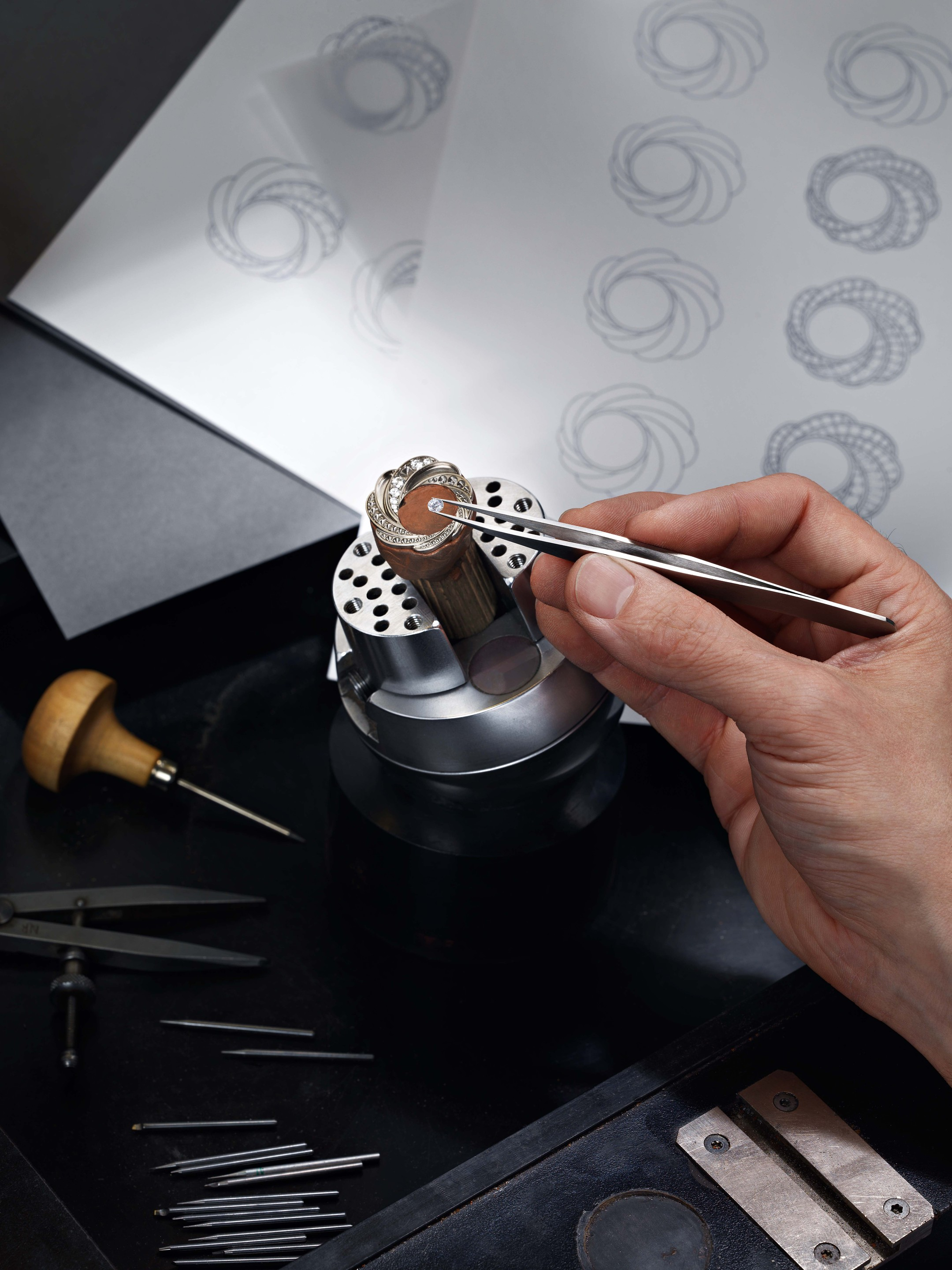 A master craftsman meticulously sets each diamond by hand based on sketches of the swirling Aria design for the new De Beers watches.
