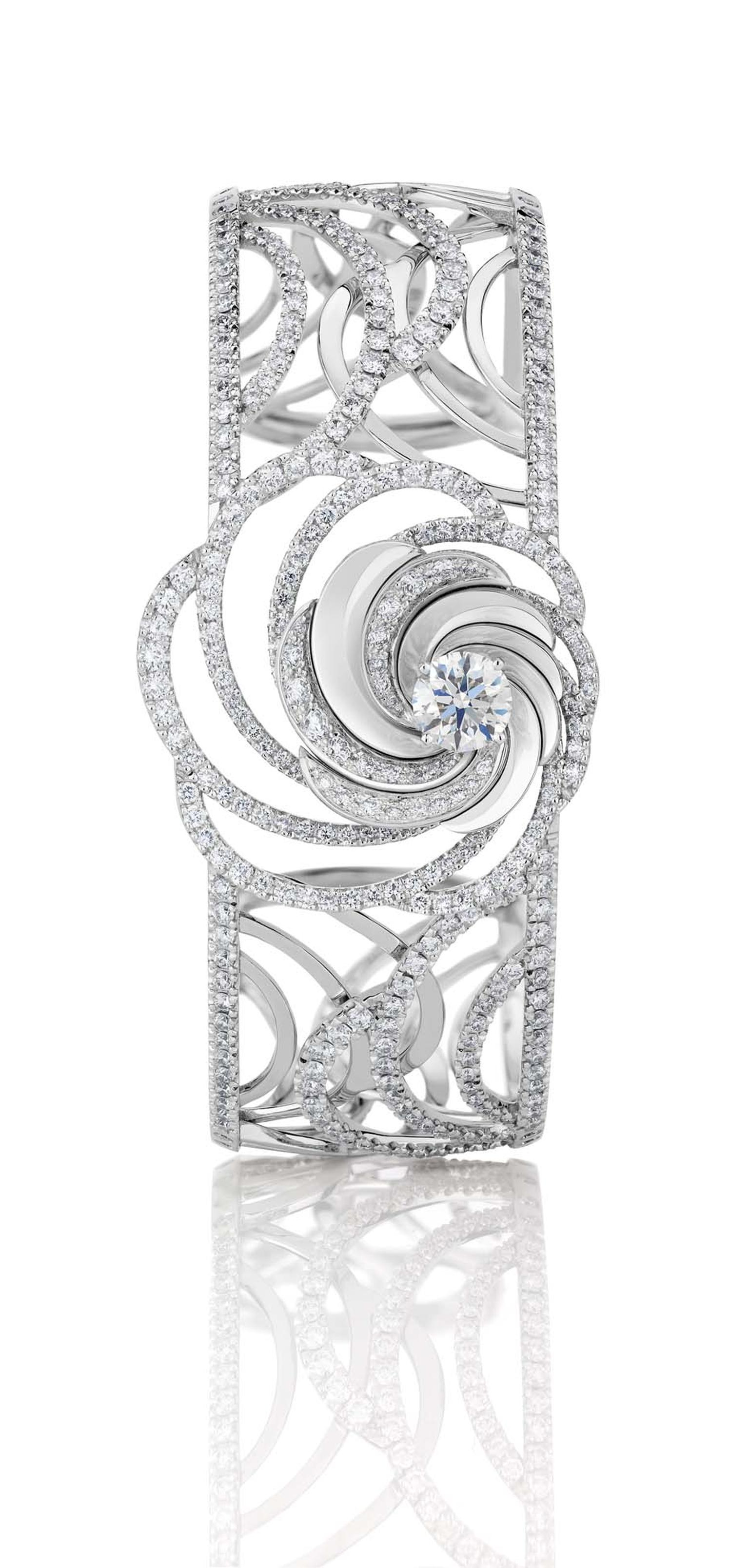De Beers Aria diamond bracelet, with a series of swirling white gold ribbons set with pavé diamonds surrounding a central brilliant-cut diamond.