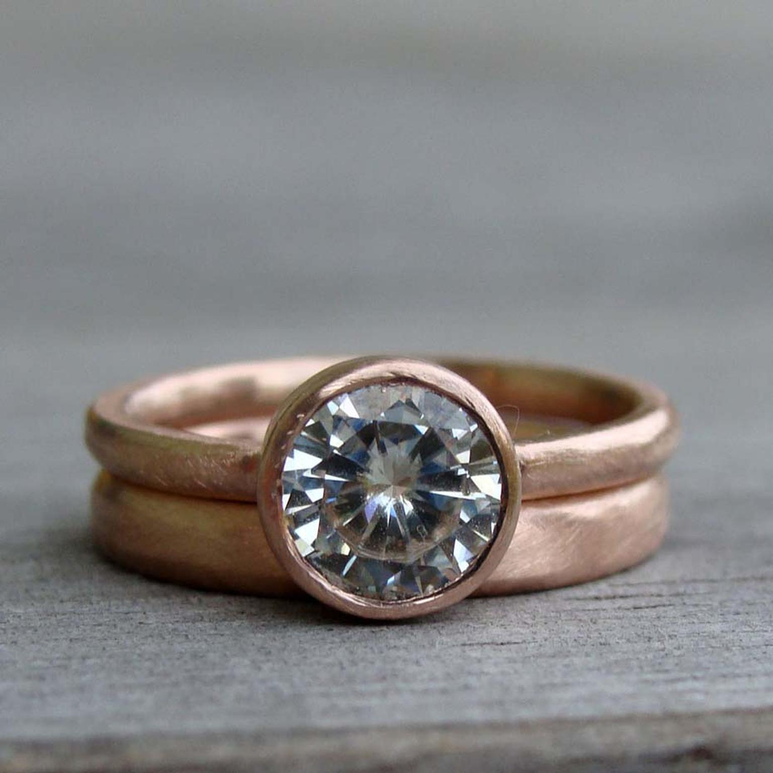McFarland Designs engagement ring featuring a Forever Brilliant Moissanite stone with a recycled rose gold band and matching wedding ring.