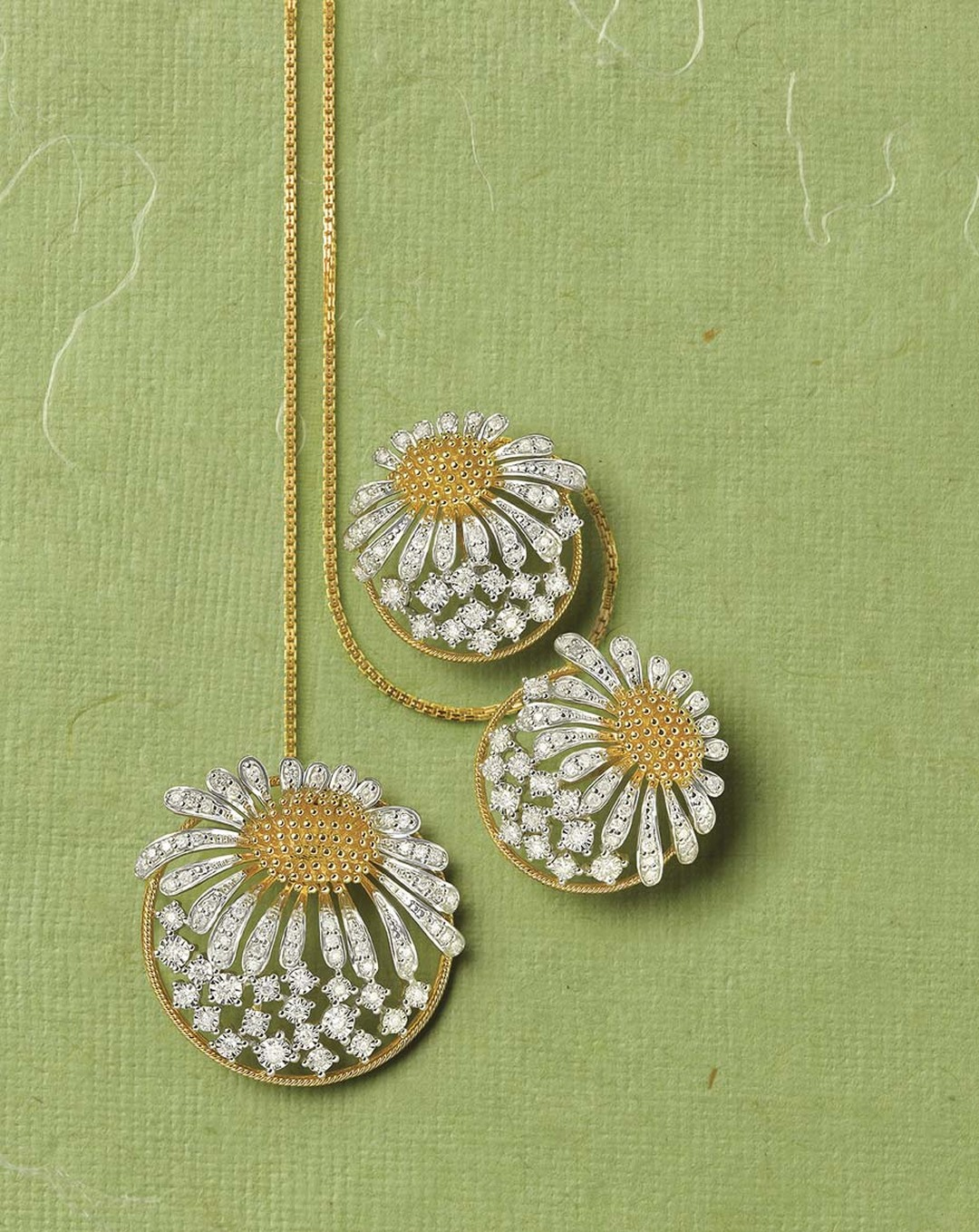 Tanishq Zyra collection white and yellow gold sunflower earrings and necklace studded with white diamonds.