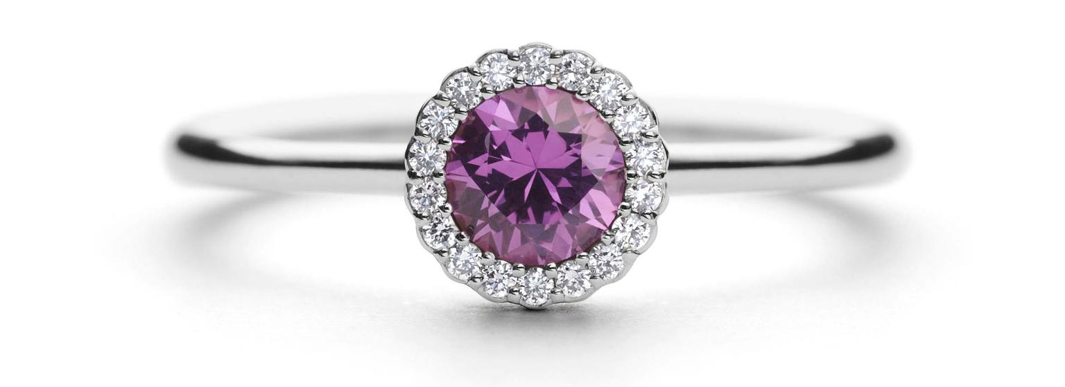 Andrew Geoghegan Cannelé engagement ring in white gold with a brilliant-cut pink sapphire encircled by diamonds.