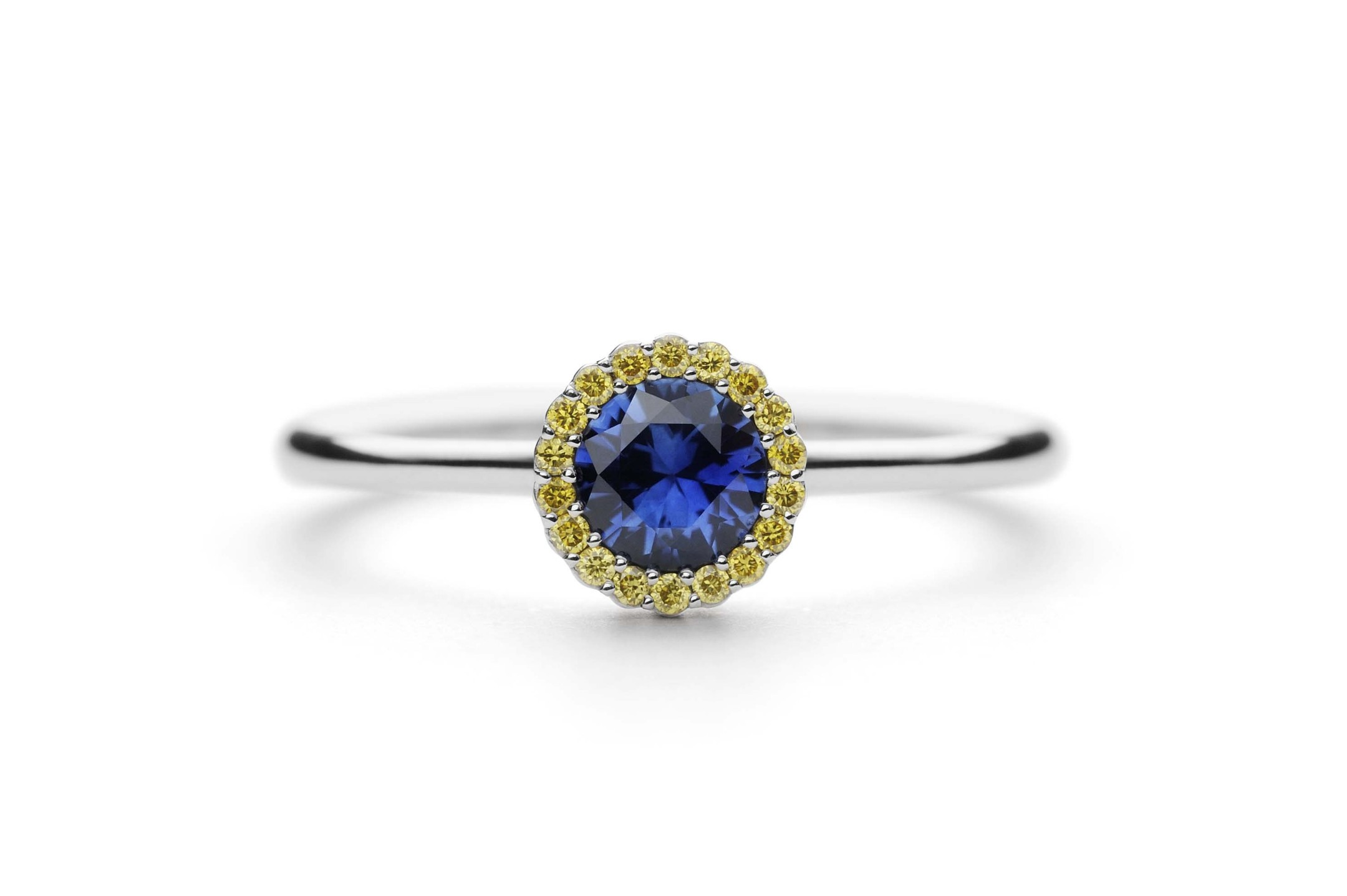Andrew Geoghegan Cannelé engagement ring in white gold with a brilliant-cut blue sapphire encircled by yellow sapphires.