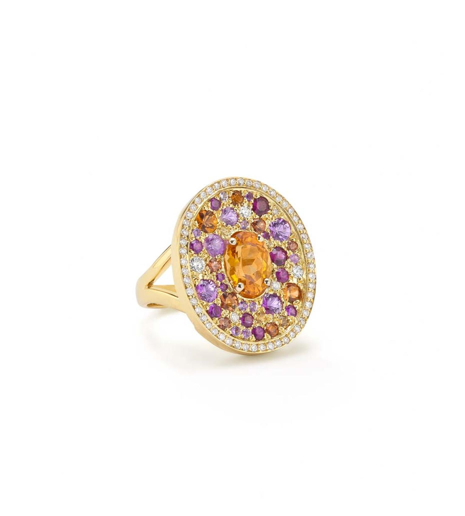 Robinson Pelham white gold Volcano Asteroid ring featuring a central oval mandarin garnet surrounded by a pave of diamonds, rubies and yellow, orange and pink sapphires.