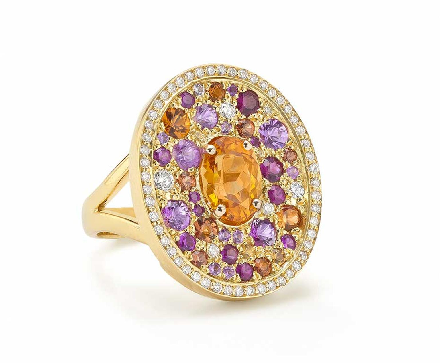 Robinson Pelham white gold Volcano Asteroid ring featuring a central oval mandarin garnet surrounded by a pavé of diamonds, rubies and yellow, orange and pink sapphires.