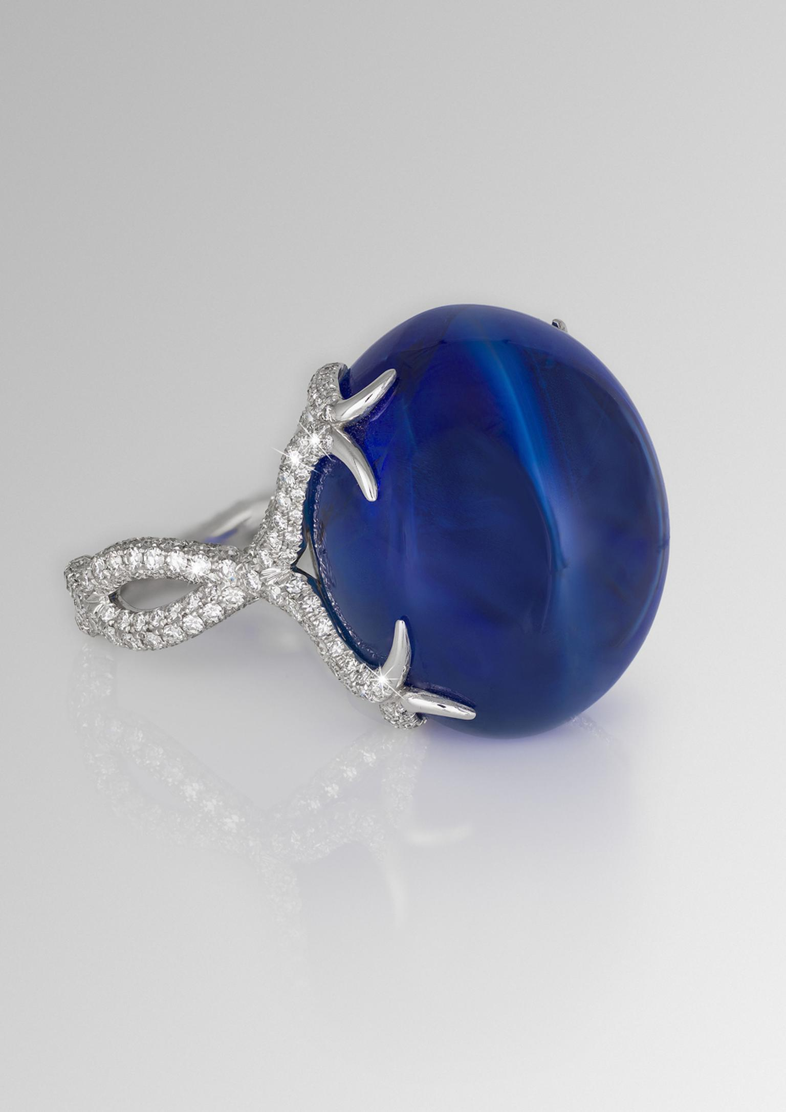 David Morris ring featuring a central 64.55ct blue Burmese double cabochon sapphire with a twisting diamond band.