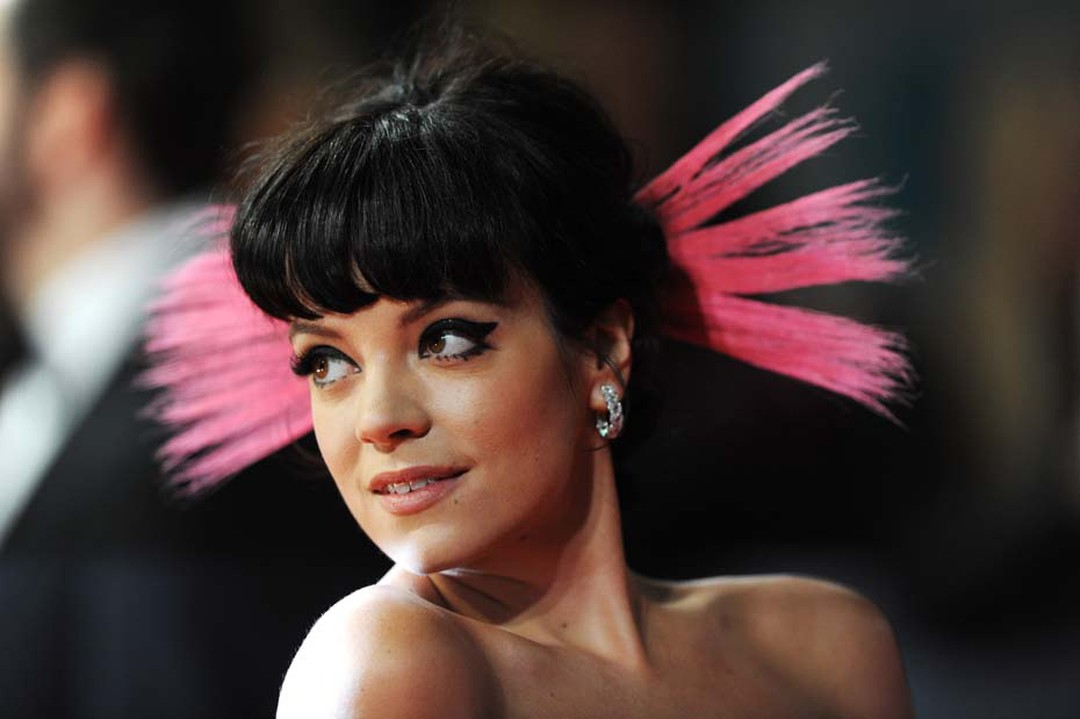 Lily Allen teamed her Vivienne Westwood dress with a classic pair of David Morris diamond Rose-Cut hoop earrings and a fluorescent hair accessory.