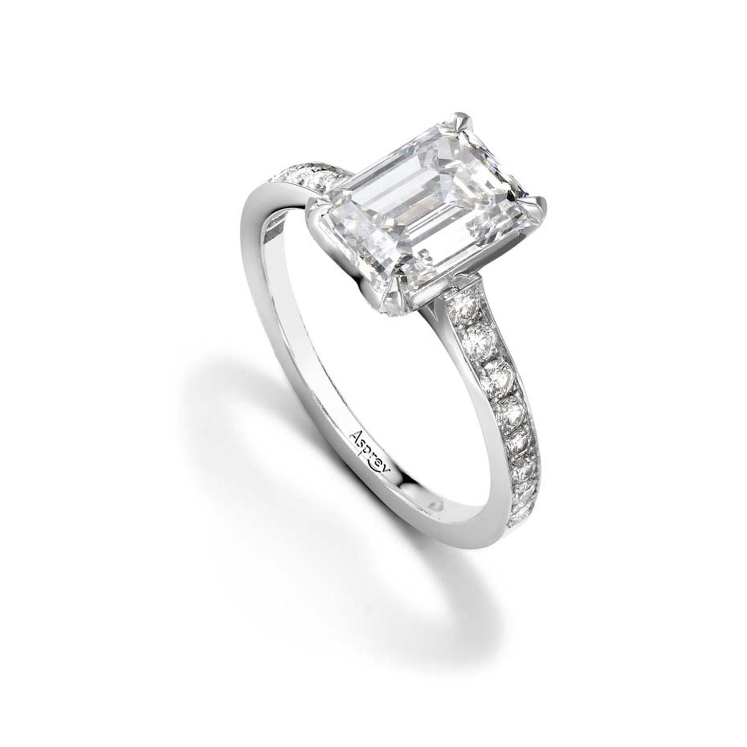 Asprey emerald-cut diamond engagement ring set with round brilliant diamonds on a platinum band.