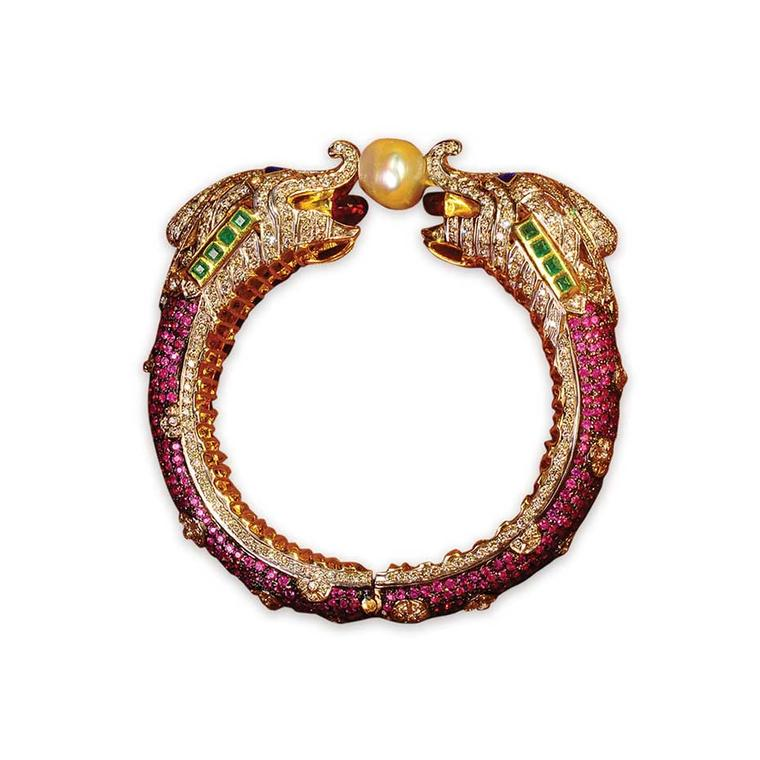 Golecha intricately crafted bangle featuring two elephants holding a pearl, studded with diamonds, rubies and emeralds.