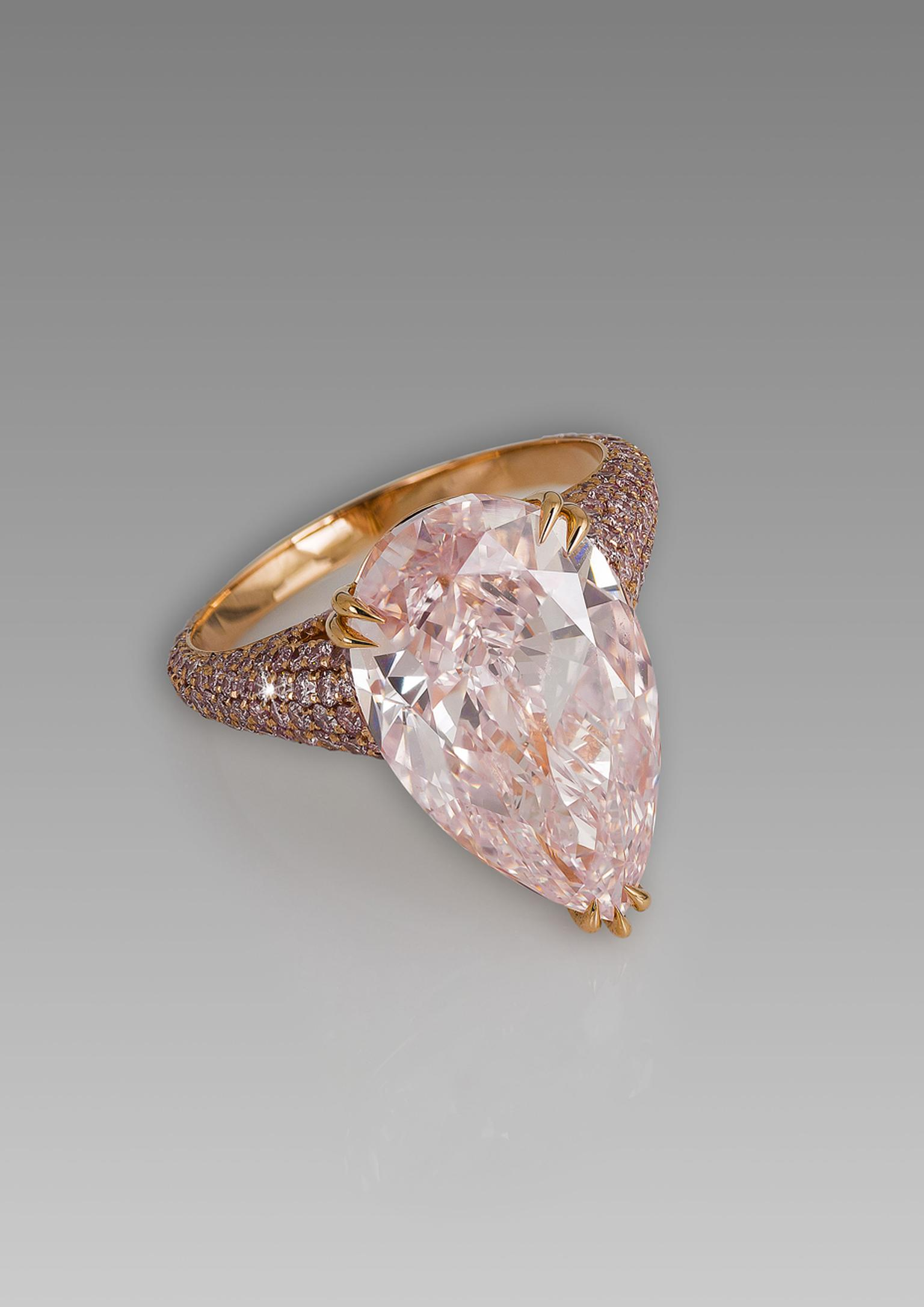 David Morris pear-shaped pink diamond ring set against a glimmering backdrop of pavé pink diamonds on a rose gold band.
