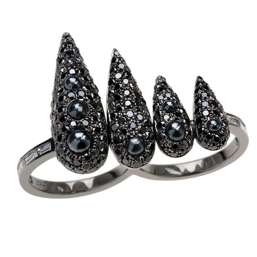 Nikos Koulis black diamond and rhodium ring featuring cascading proportions offset by the white diamond baguettes on its shoulders.