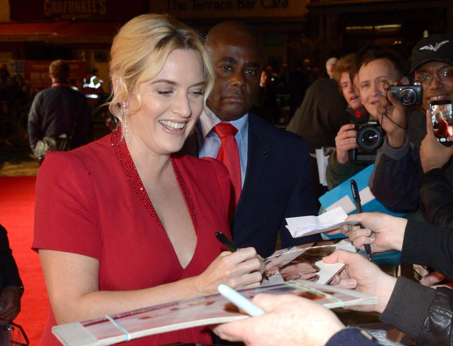 Kate Winslet signing autographs on the red carpet of the BFI London Film Festival. Image by: IWC/David M. Benett.