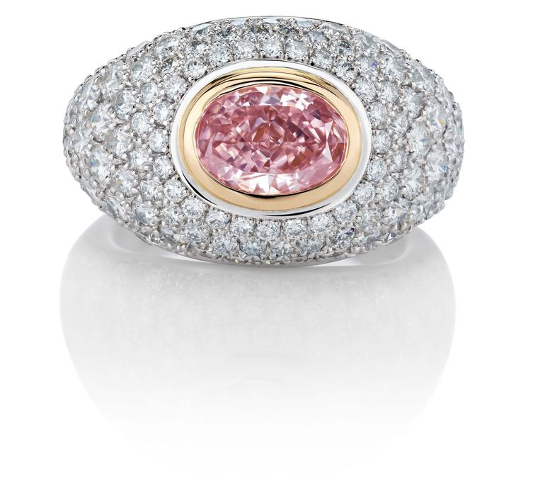 De Beers 1888 Creative Solitaires Aurora ring, with an oval Fancy Intense pink diamond surrounded by a pavé of round brilliant diamonds.