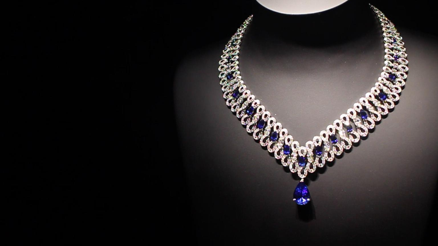 Extremely Piaget collection Infinity necklace with diamonds intertwining like ribbon underneath pear-shaped sapphires and diamonds leading to a dangling sapphire pear-shaped drop.