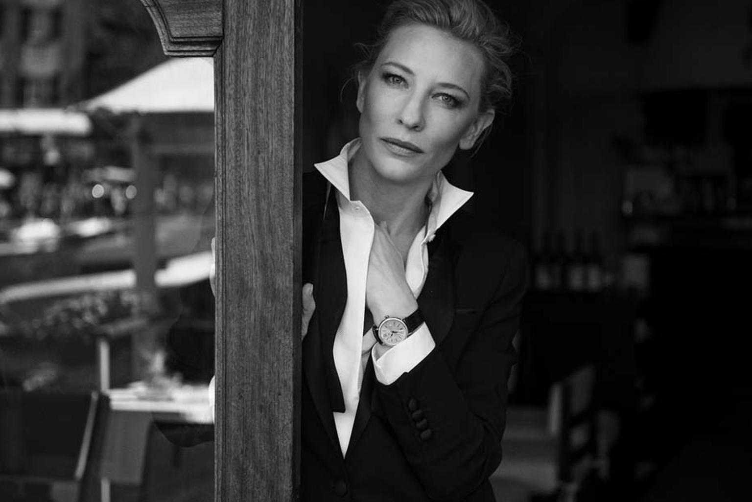 Wearing the IWC Portofino Midsize Automatic Day & Night watch featuring a red gold case set with 66 diamonds, Cate Blanchett looks on with sultry eyes at the camera.