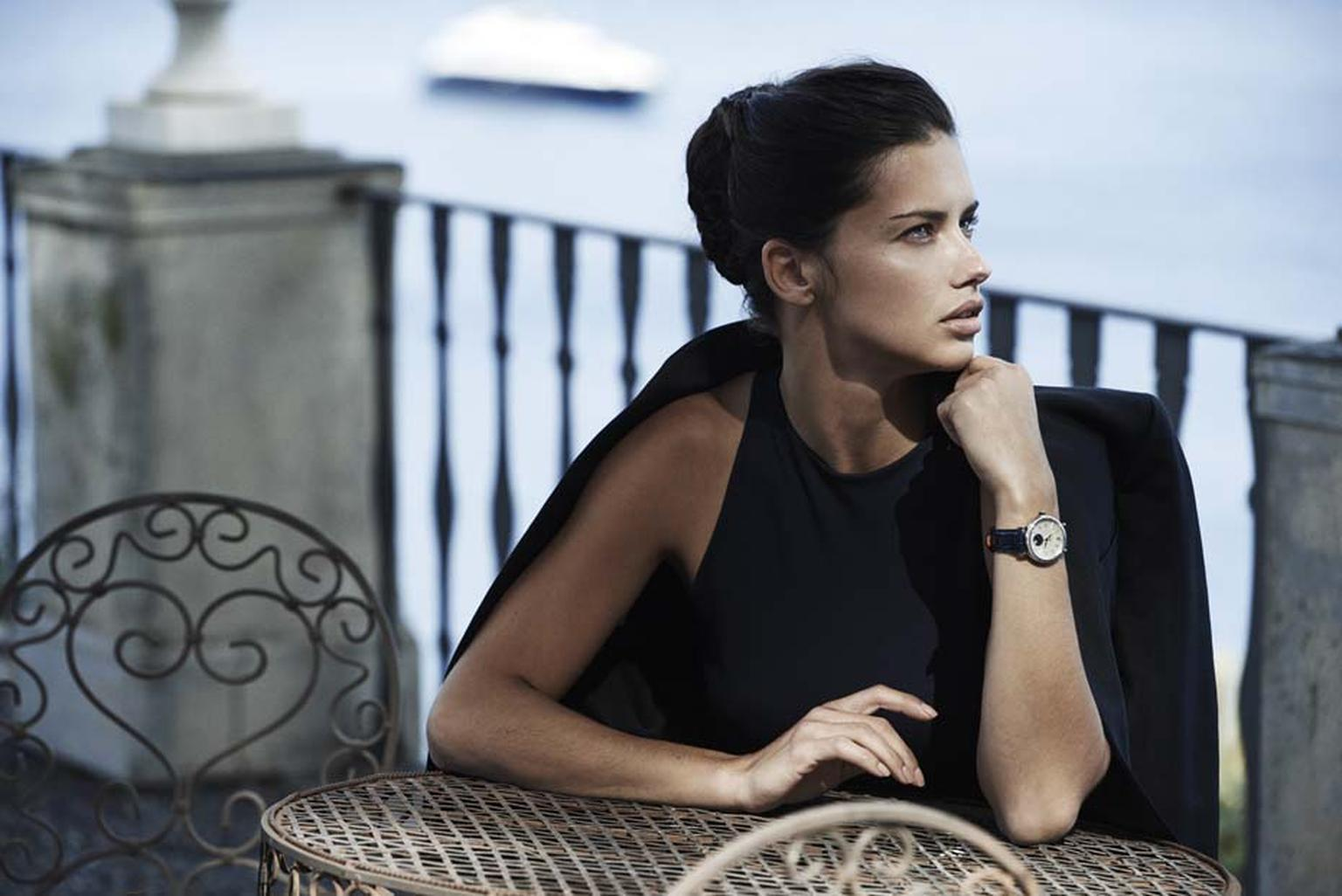 Adriana Lima looks to the Portofino seaside while wearing the IWC Schaffhausen Portofino Midsize Automatic Moon Phase watch with an alligator leather strap.