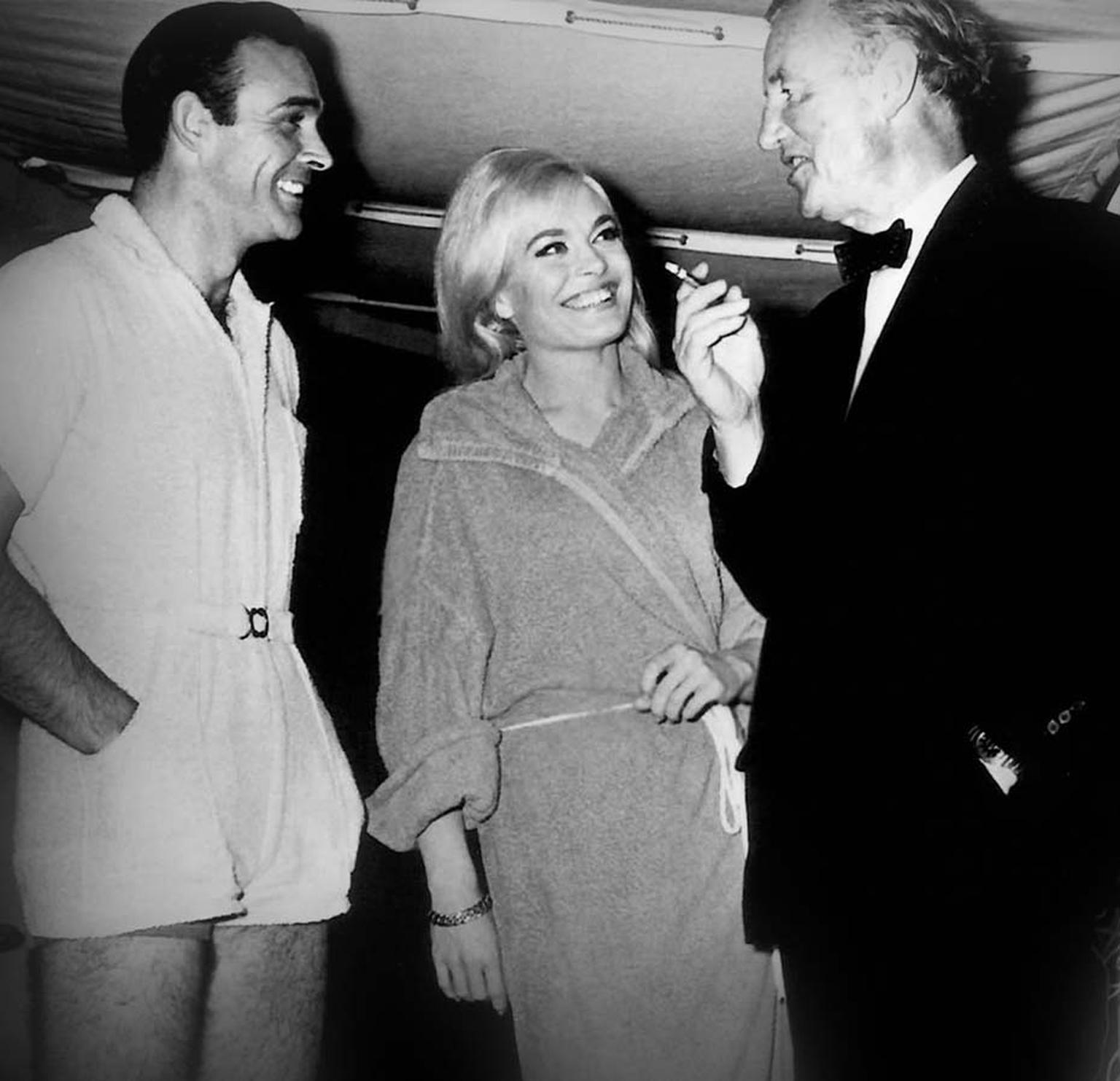 Ian Fleming chatting with Sean Connery and Honor Blackman on the set of Goldfinger. Fleming was a die-hard Rolex fan, with his watch of choice being the Rolex Oyster Explorer.