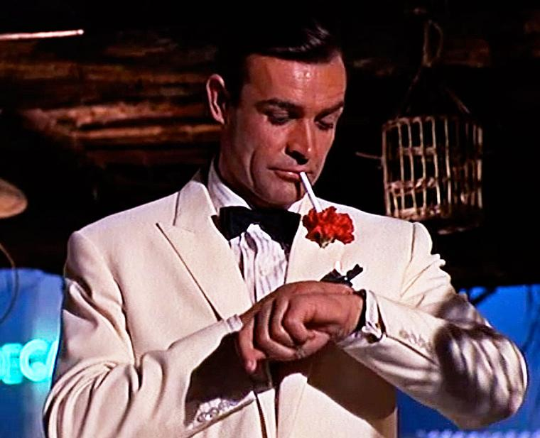 Sean Connery as 007 checking the time on his Rolex Submariner watch with a striped nylon strap during Goldfinger, the third Bond film.
