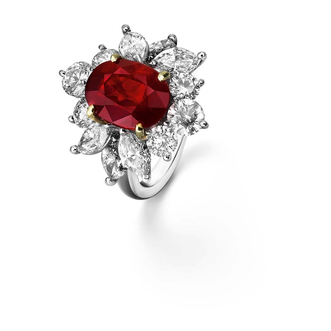 Asprey ruby engagement ring in platinum framed with triangular diamond shoulders.