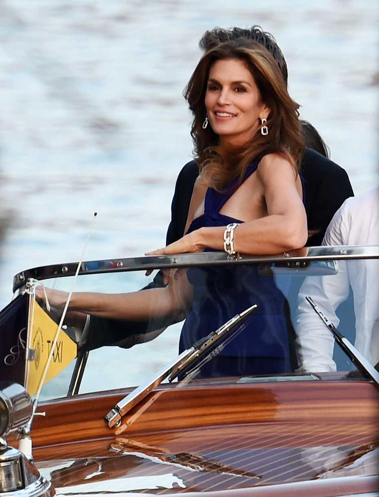 Cindy Crawford makes her way to the wedding of George Clooney and Amal Alamuddin by speedboat wearing Harry Winston Diamond Links bracelet and earrings.