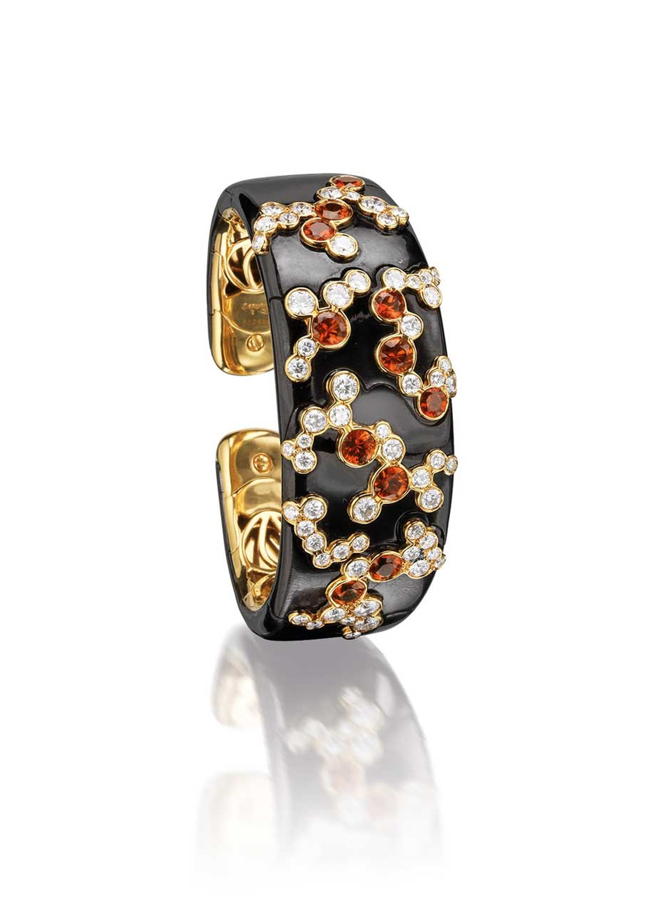 Marina B hinged bangle, influenced by Japanese culture and the cherry blossom. The bangle features brilliant-cut diamonds and circular-cut orange sapphires (estimate: £10,900-15,600).