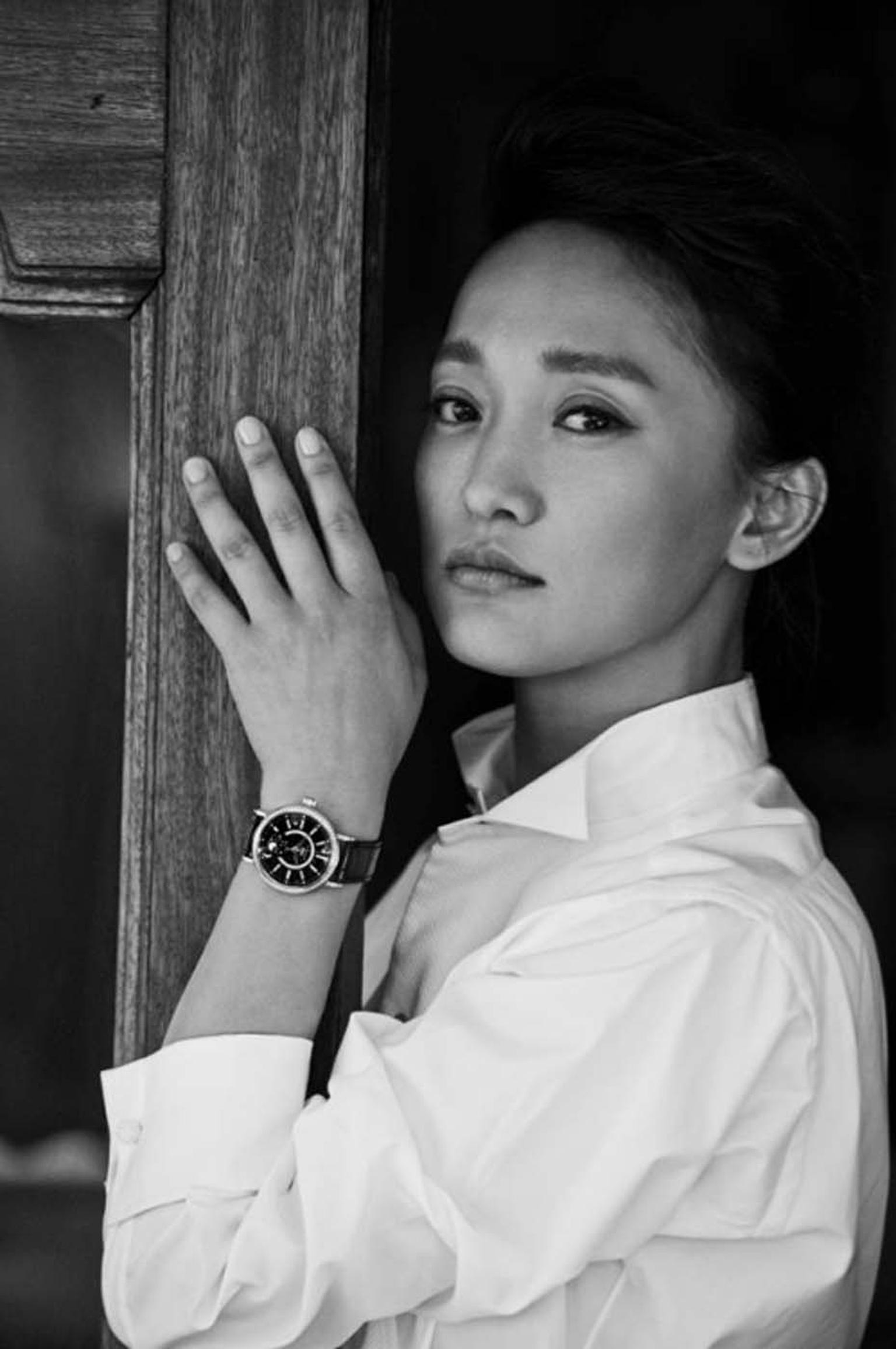 Zhou Xun wearing the IWC Portofino Midsize Automatic Moon Phase watch with a black mother-of-pearl dial and an alligator strap.